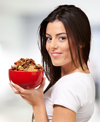 portrait of young woman holding a cereal bowl indoor
