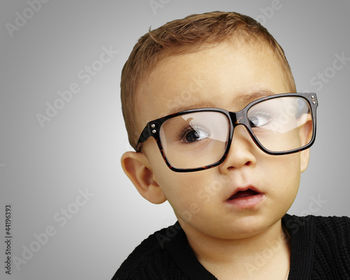 portrait of kid wearing glasses over grey background