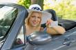 Junge Frau im Cabrio zeigt ihren Führerschein