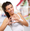 portrait of young healthy girl gesturing heart symbol at street