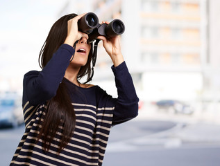 portrait of young girl looking through a binoculars at city