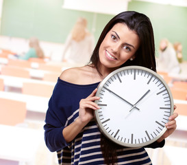 portrait of young woman holding clock at classroom