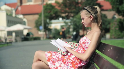 Young attractive woman reading book in the city