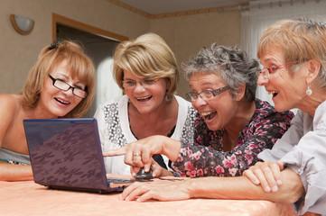 Senior - femmes joyeuses utilisant un ordinateur en groupe