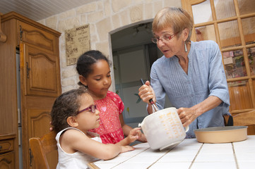 Senior - grand-mère préparant un gâteau avec ses petits-enfants