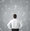 Young businessman looking at many question marks
