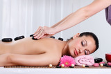 Beautiful woman receiving hotstone massage at spa