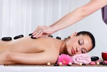Beautiful woman receiving hotstone massage at spa