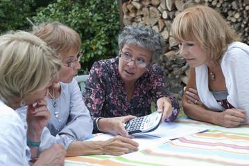 Senior - Femme calculant à l'aide d'une calculatrice