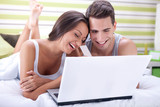 Couple in bed buying on-line with credit card