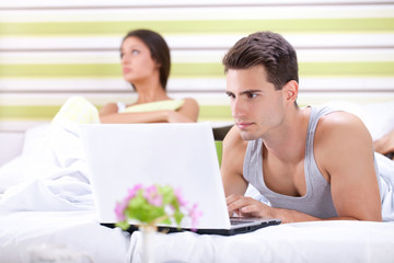 Unhappy woman because his husband working in bed