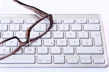 Brille liegt auf einer weißen Computertastatur