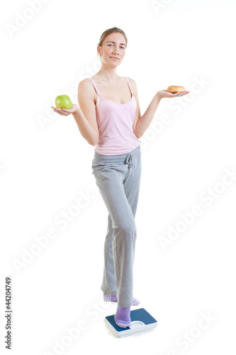 young beautiful woman choosing between burger and apple
