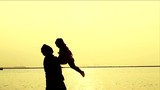 Silhouette of Father and Daughter at Beach