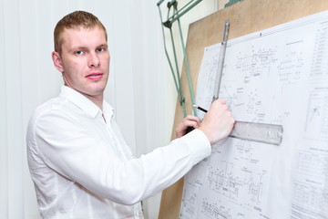 Engineer with blueprint standing near old drawing board