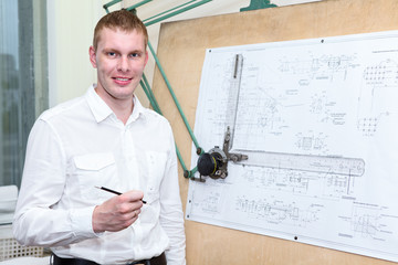 Engineering worker with pencil in workplace near panel board