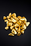 Many gold nuggets on a black background.