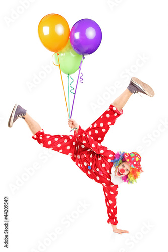 Clown holding balloons and standing on one hand
