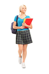 Full length portrait of a smiling school girl walking and holdin
