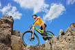 Person riding a mountain bike amid rocks on a sunny day against