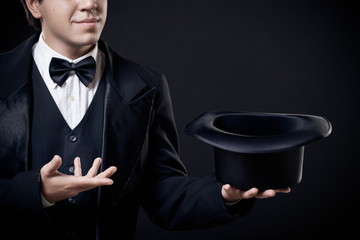 closeup of magician showing tricks with top hat isolated