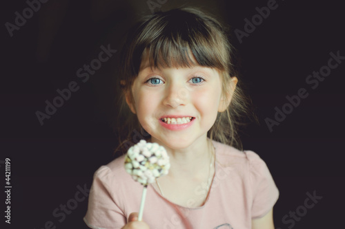 Funny child girl showing a marshmallow cake
