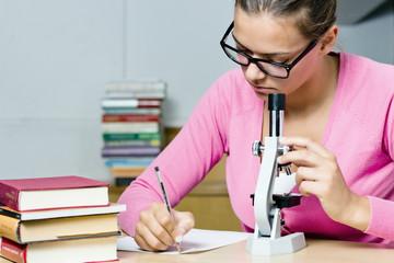 Ragazza studia con microscopio