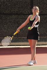 Female High School Tennis Player Prepares To Serve