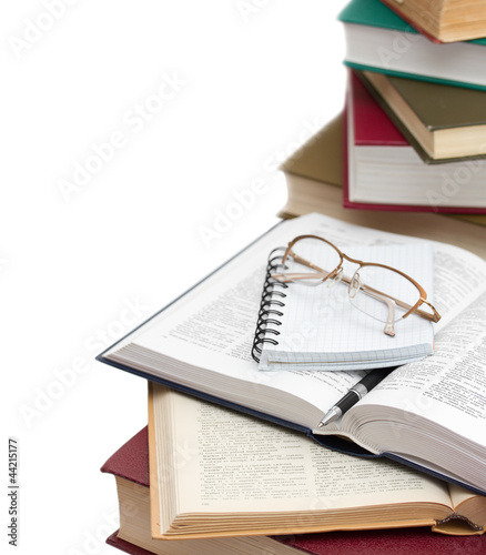 opened dictionaries, lying with a glasses, note and pen against