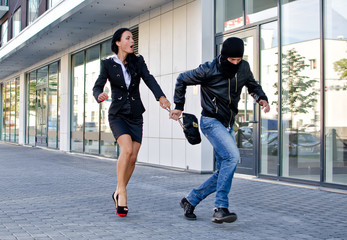 Bandit stealing businesswoman bag in the street