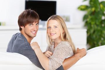 lächelndes paar sitzt auf dem sofa