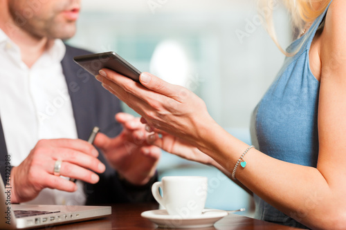 Working colleagues - man and woman - sitting in cafe
