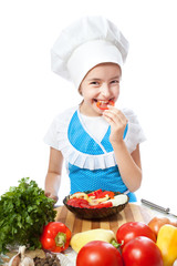 Happy little chef cook tastes salad with Bell Pepper