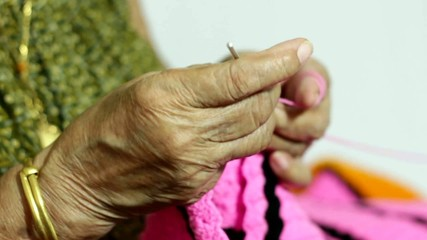 female elder knitting hand close up