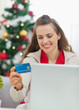 Happy young woman making Christmas shopping on internet