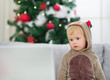 Thoughtful baby in deer suit near Christmas tree looking in lapt