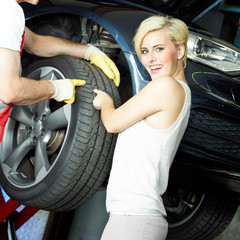 Customer and mechanic check the tread pattern of a summer tyre