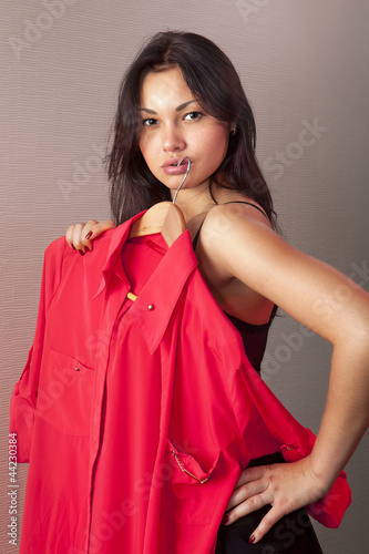 girl which tries on red shirt in shop
