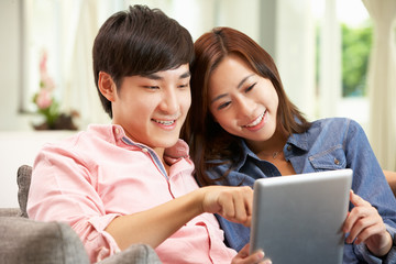 Young Chinese Couple With Digital Tablet Whilst Relaxing On Sofa