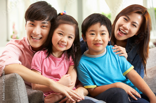 Chinese Family Relaxing On Sofa At Home