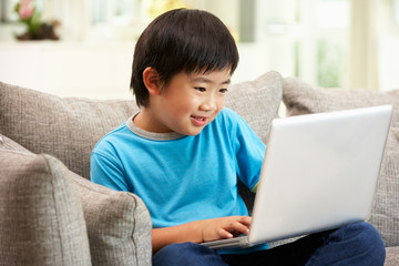 Young Chinese Boy Using Laptop Whilst Sitting On Sofa At Home