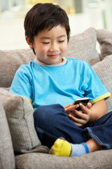 Young Chinese Boy Using Mobile Phone On Sofa At Home