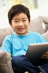 Young Chinese Boy Using Tablet Computer Whilst Sitting On Sofa
