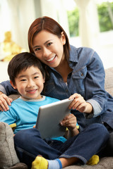 Chinese Mother And Son Using Tablet Computer Whilst On Sofa