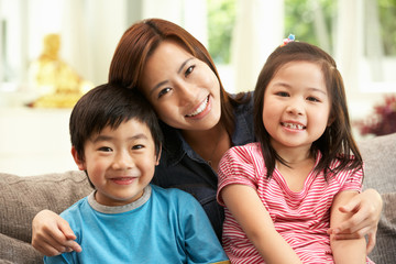Chinese Mother And Children Sitting On Sofa At Home Together