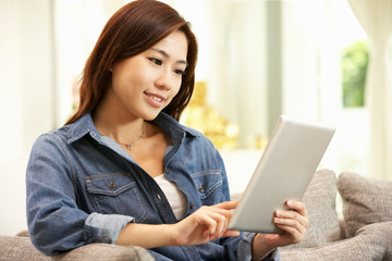 Young Chinese Woman Using Digital Tablet Whilst Relaxing On Sofa