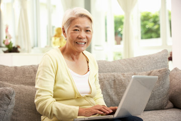 Senior Chinese Woman Using Laptop Relaxing On Sofa At Home