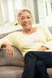 Senior Chinese Woman Relaxing On Sofa At Home