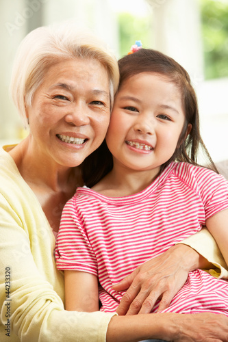 Chinese Grandmother And Granddaughter Relaxing On Sofa At Home