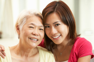 Portrait Of Chinese Mother With Adult Daughter Relaxing At Home